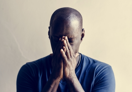 Black man with hands covered his face feeling worried Banco de Imagens