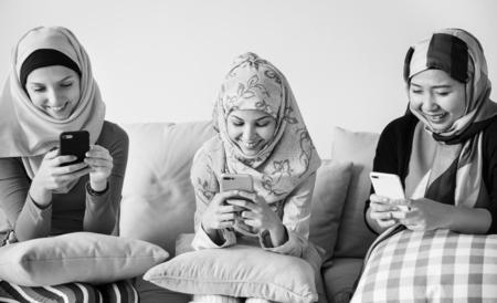 Monochrome image of muslim women using a phone