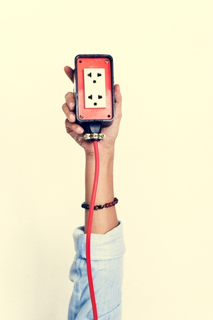 Hand holding electric outlet isolated on background Stockfoto