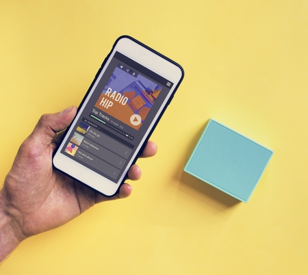 Hand holding smartphone connect to bluetooth speaker