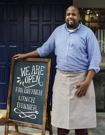 A cheerful business owner standing with open blackboard