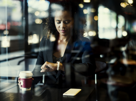 Woman looking at her watch at cafe Imagens