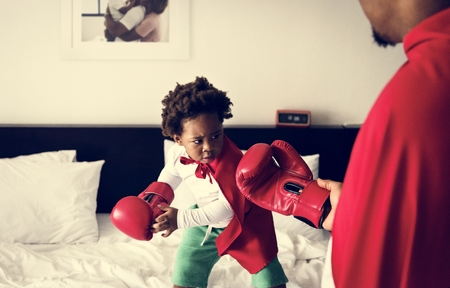 African descent kid wearing robe doing boxing with dad on the bed 版權商用圖片