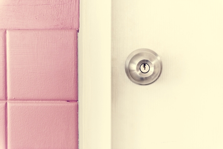 Closeup of stainless steel door knob on white door