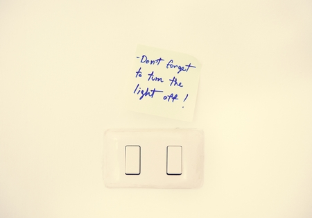 Electric light switch with reminder note on white wall