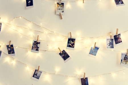 Photos hanging with decoration lights on the white wall