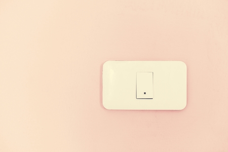 White light switch electric power supply on pink wall