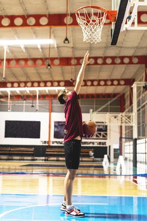 Caucasian teenage boy on a basketball goal and aim concept