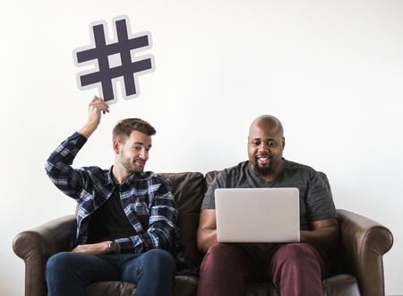 Men using laptop sitting on sofa