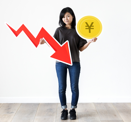 Unhappy Asian woman holding a Japnese Yen and financial decrease arrow