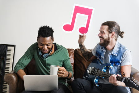 African American and Caucasian male in a songwriting process holding musical note Stock Photo