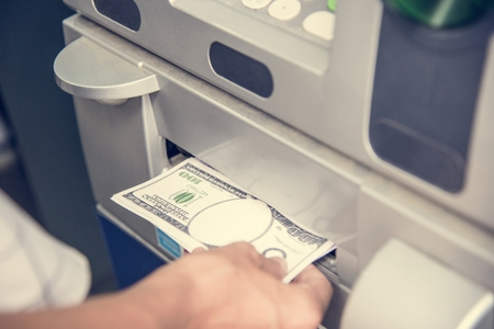 Closeup of a hand getting money from an ATM