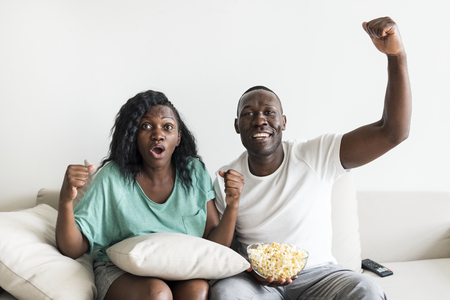 Couple cheering on their sofa Фото со стока