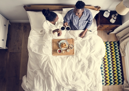 African American couple in bed having a breakfast in bed