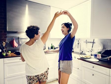 Lesbian couple dancing in the kitchen Reklamní fotografie