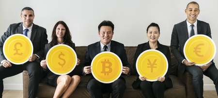 Business people holding currency icons Stock Photo
