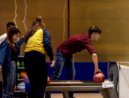 Caucasian boy picking up a bowling ball hobby and leisure concept Stok Fotoğraf