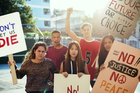 Grupo de adolescentes que protestaban contra la manifestación sosteniendo carteles concepto de paz de justicia pacifista