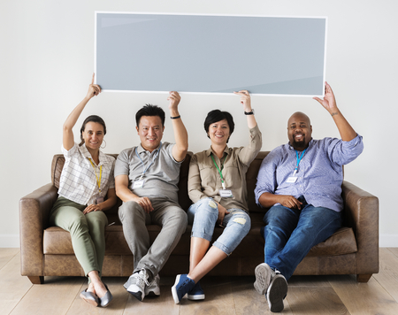 Diverse workers sitting on couch holding empty banner