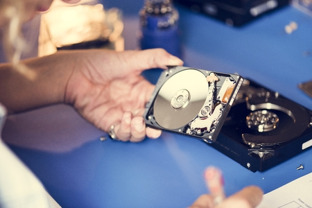 Hand hold HDD to fix at workshop station Stock Photo