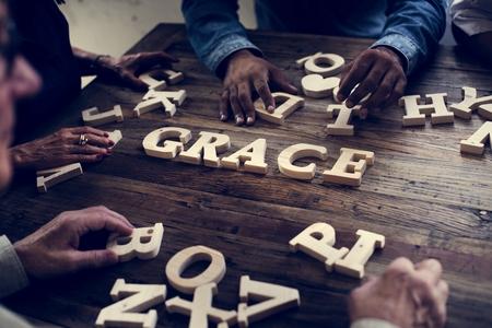 Una parola di grazia dell'alfabeto in legno sul tavolo