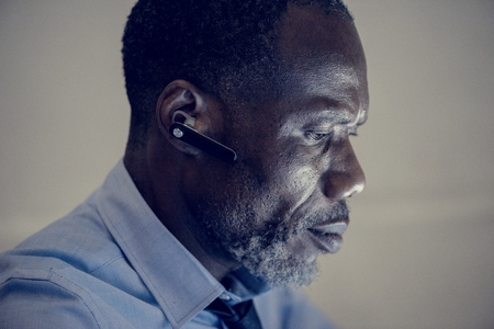 African ethnicity businessman with bluetooth earphone