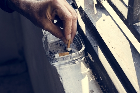 Closeup of hand smoking cigarette with ashtray Stock Photo