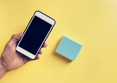 Hand holding smartphone and bluetooth speaker Stock Photo