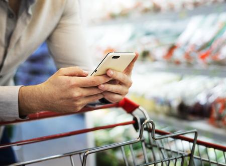 Man speelt met zijn telefoon bij supermarkt