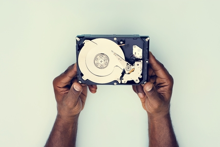 Hands holding Hard disk drive data backup isolated on background