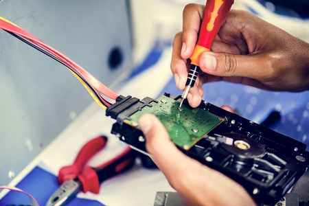 Closeup of hands with screwdriver with computer hard disk