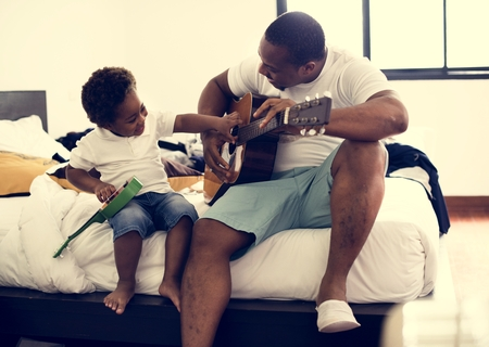 Black father enjoy playing guitar with his child together happiness