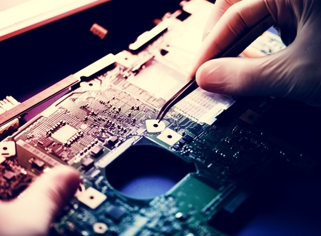 Closeup of hands working on computer motherboard