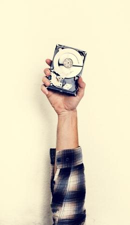 Hand, die Computerfestplattenlaufwerk lokalisiert auf Weiß hält