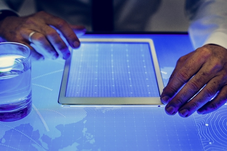 Hands on digital tablet on cyber space table