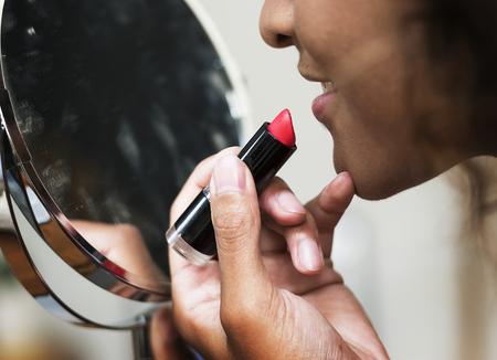 Woman putting on lipstick at mirror 写真素材