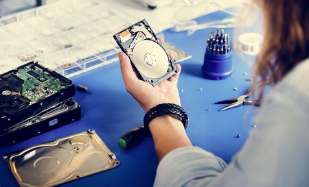 Technician holding HDD fixing at electronic repair shop Stock Photo
