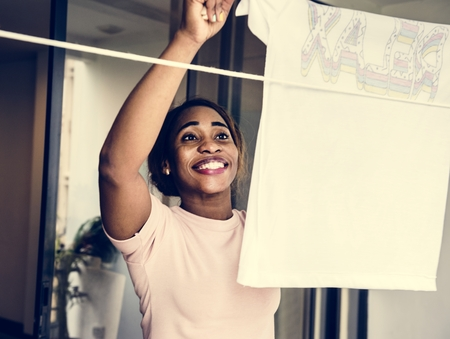 Closehup of black woman hanging washed clothes housework Reklamní fotografie