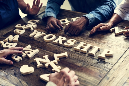 Group of people arrangement a word on wooden table Stockfoto