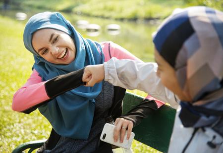 Muslim women fist bumping each other