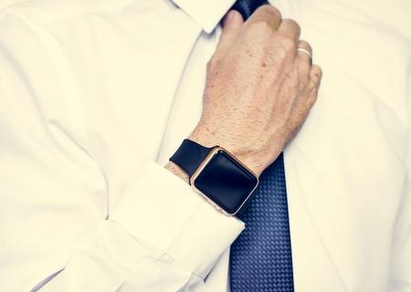 Hand with smartwatch adjust necktie Stock Photo