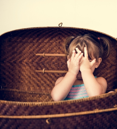 Little girl sitting in the basket and hands covering face 版權商用圖片