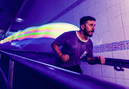 Man in a running movement with long exposure light at his back