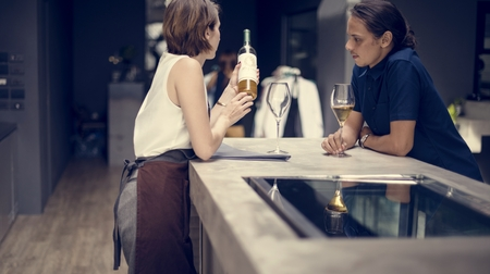 Bartender showing a wine to customer at the bar