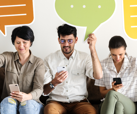 Co-workers sitting on couch and holding message icons