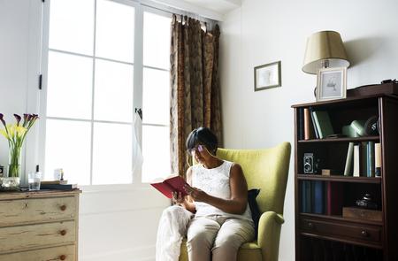 Senior woman reading book in the room Standard-Bild - 109676594