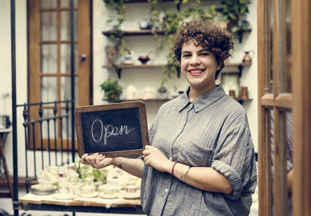Shop owner holding an open sign Banque d'images - 109689954