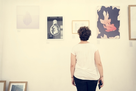 People looking at frames in exhibition