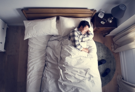 Japanese man sleeping on bed 写真素材
