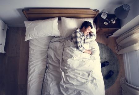 Japończyk śpi na łóżku